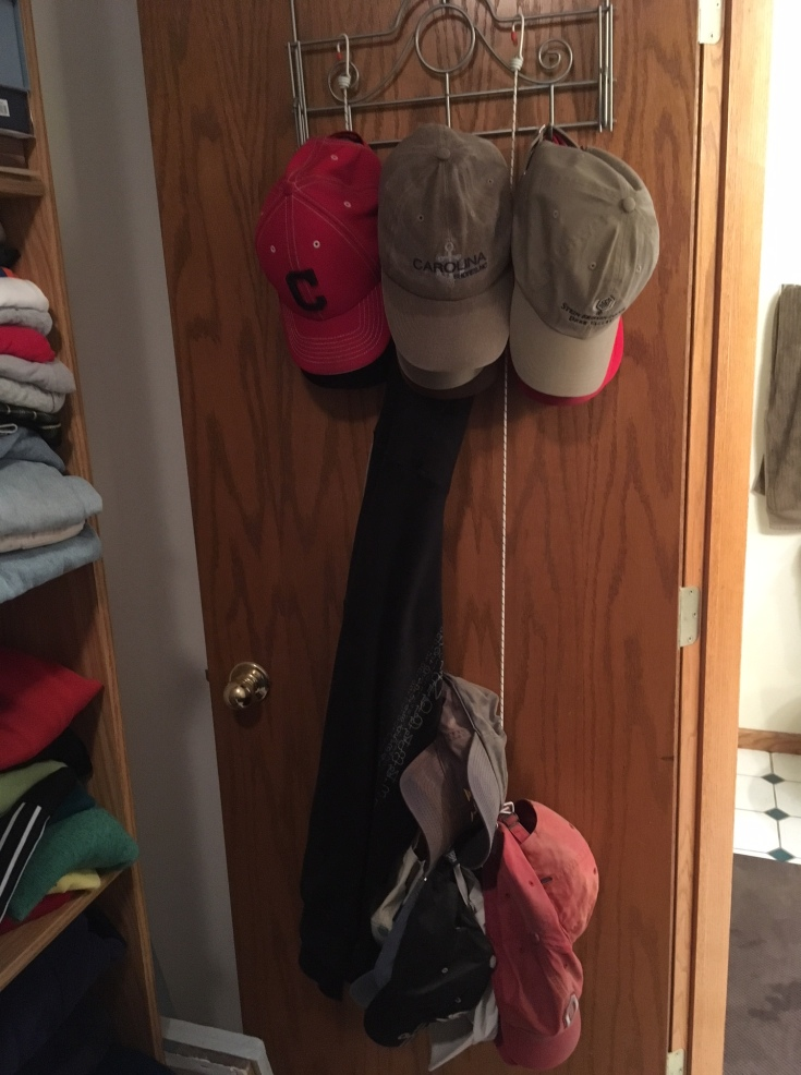 22 hats hanging in a dad's closet