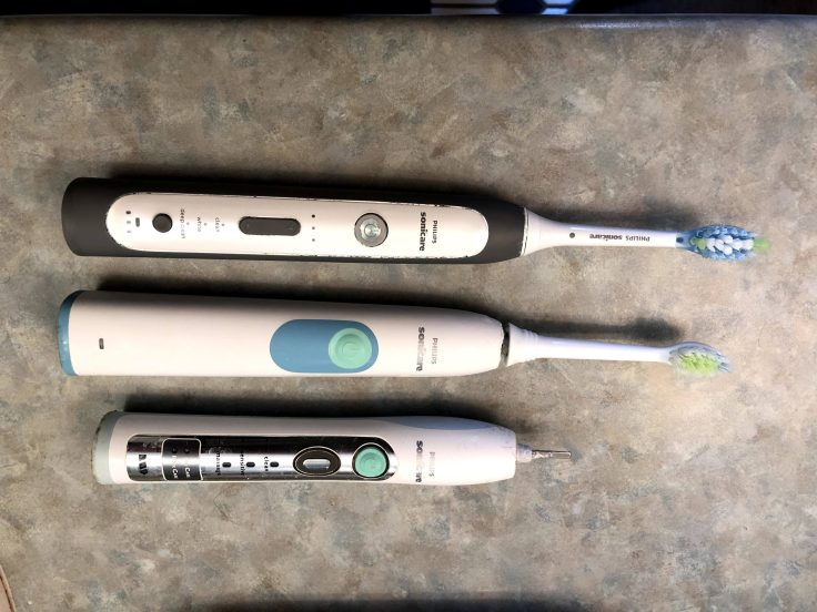 Three electric toothbrushes in various states of use